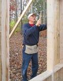 Carpintero que clava el forro de la madera contrachapada Imagenes de archivo
