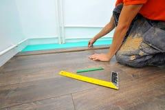 Carpintero que hace el trabajo laminado del piso imagenes de archivo