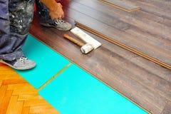 Carpintero que hace el trabajo laminado del piso fotografía de archivo libre de regalías