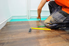 Carpintero que hace el trabajo laminado del piso fotos de archivo