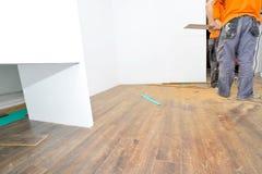 Carpintero que hace el trabajo laminado del piso imagen de archivo libre de regalías