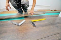Carpintero que hace el trabajo laminado del piso foto de archivo