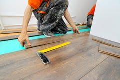 Carpintero que hace el trabajo laminado del piso imagen de archivo