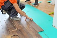 Carpintero que hace el trabajo laminado del piso fotografía de archivo