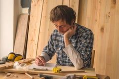 Carpintero que hace notas del proyecto de la artesanía en madera en el papel del tablero imágenes de archivo libres de regalías