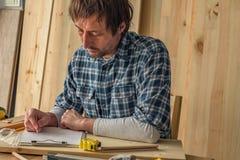 Carpintero que hace notas del proyecto de la artesan?a en madera en el papel del tablero foto de archivo