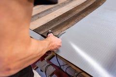 Carpintero que hace su trabajo en taller de la carpintería un hombre en un taller de la carpintería mide y lamina de los cortes fotos de archivo