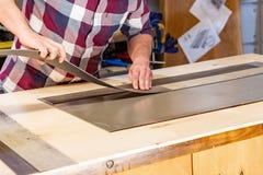 Carpintero que hace su trabajo en taller de la carpintería un hombre en un taller de la carpintería mide y lamina de los cortes imágenes de archivo libres de regalías