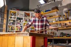 Carpintero que hace su trabajo en taller de la carpintería un hombre en un taller de la carpintería mide y lamina de los cortes imagenes de archivo