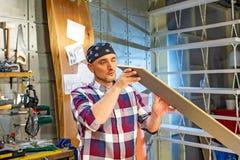 Carpintero que hace su trabajo en taller de la carpintería un hombre en un taller de la carpintería mide y lamina de los cortes foto de archivo libre de regalías