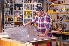Carpintero que hace su trabajo en taller de la carpintería un hombre en un taller de la carpintería mide y lamina de los cortes foto de archivo