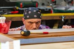 Carpintero que hace su trabajo en taller de la carpintería un hombre en un taller de la carpintería mide y lamina de los cortes imagen de archivo