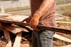 Carpintero que lleva un tablón de madera grande en sus manos Foto de archivo libre de regalías