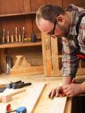 Carpintero que marca una medida en un tablón de madera Fotos de archivo