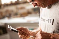 Carpintero que mide con su calibrador Imagen de archivo