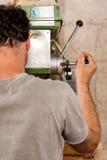 Carpintero que perfora un tablón con maquinaria Imagenes de archivo