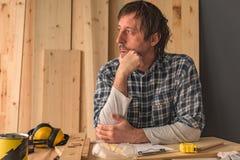 Carpintero que piensa en interior del taller de la artesanía en madera de la pequeña empresa imagenes de archivo