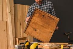 Carpintero que repara el cajón de madera en taller de la artesanía en madera fotografía de archivo libre de regalías