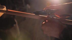 Carpintero que trabaja con un cuchillo Corta la envoltura a lo largo de la barra de madera metrajes