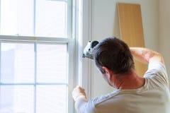 Carpintero que usa el arma a los moldeados en ventanas, ajuste que enmarca del clavo, Foto de archivo libre de regalías