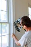 Carpintero que usa el arma a los moldeados en ventanas, ajuste que enmarca del clavo, Foto de archivo