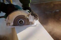 Carpintero que usa la sierra de la circular para las tablas de cortar Detalles de la construcción del trabajador de sexo masculin Foto de archivo libre de regalías