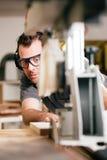 Carpintero que usa la sierra eléctrica Fotografía de archivo libre de regalías