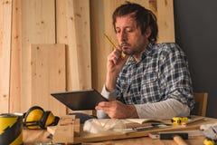 Carpintero que usa la tableta digital en taller de la artesanía en madera de la pequeña empresa fotos de archivo