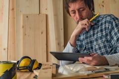 Carpintero que usa la tableta digital en taller de la artesanía en madera de la pequeña empresa foto de archivo libre de regalías