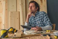Carpintero que usa la tableta digital en taller de la artesan?a en madera de la peque?a empresa fotos de archivo libres de regalías