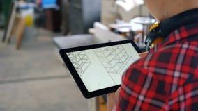 Carpintero que usa la tableta en el taller que mira el diseño de muebles en la pantalla almacen de metraje de vídeo