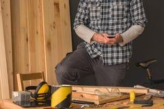 Carpintero que usa smartphone en taller de la artesanía en madera de la pequeña empresa imagen de archivo libre de regalías