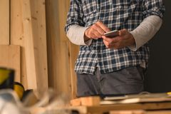 Carpintero que usa smartphone en taller de la artesanía en madera de la pequeña empresa fotos de archivo libres de regalías