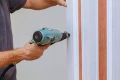 Carpintero que usa un arma del clavo del clavito para terminar la escopeta de aire comprimido del ajuste que enmarca para clavar Fotografía de archivo