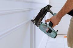 Carpintero que usa un arma del clavo del clavito para terminar el ajuste que enmarca Imagen de archivo