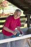 Carpintero smilling feliz con la herramienta del plano de la potencia Imagen de archivo