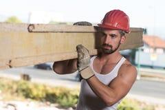 Carpintero sonriente Carrying un tablón de madera grande en su hombro foto de archivo