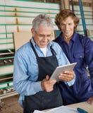 Carpintero Using Digital Tablet con el compañero de trabajo fotografía de archivo libre de regalías