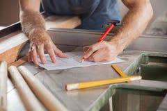 Carpintero Working On Blueprint en Tablesaw Fotografía de archivo