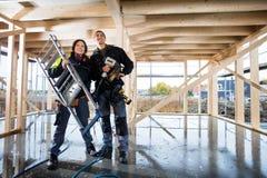 Carpinteros confiados con las herramientas que se colocan en el emplazamiento de la obra Imagenes de archivo