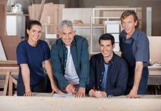 Carpinteros confiados que trabajan en taller foto de archivo