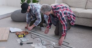 Carpinteros que aprietan el tornillo en el marco metálico en casa almacen de video