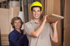 Carpinteros que llevan el tablón de madera en taller fotos de archivo libres de regalías