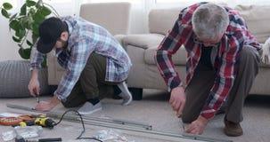 Carpinteros que usan un destornillador para atornillar en un marco met?lico metrajes