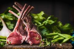 Carrè di agnello, carne cruda con l'osso sul tavolo da cucina rustico a fondo di legno immagine stock
