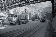 Carrara marble. Marble quarry in the mountains near Carrara - Tuscany - Italy. A lorry is being loaded with big blocks of marble for transport whie another one stock photography