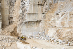 Carrara Marble quarries. Marble quarry with transporter digging sand Stock Photos