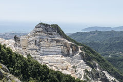 Carrara Marble quarries. Top of a marble mountain. In the background the city of Carrara and the Ligurian sea Stock Photography
