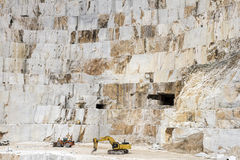Carrara Marble quarries. Two machines harvesting marble. Mountain face in the background Stock Photography