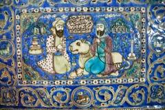 Carreaux de céramique de 19ème siècle avec un lion et deux hommes persans parlant dans le jardin Images libres de droits